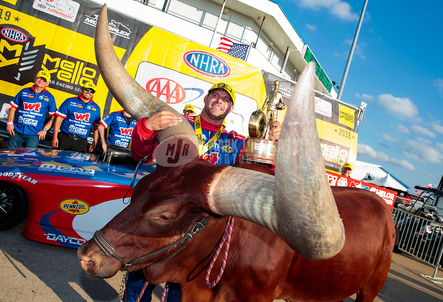 Oct 20, 2019; Ennis, TX, USA; NHRA funny car driver Matt Hagan and crew celebrate alongside a live bull after winning the Fall Nationals at the Texas Motorplex. Mandatory Credit: Mark J. Rebilas-USA TODAY Sports