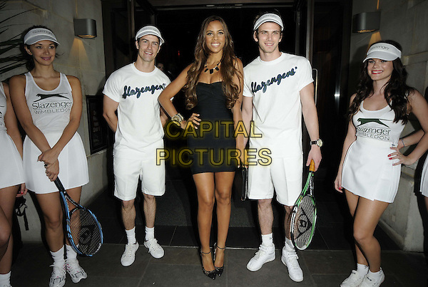 Rochelle Wiseman & models.The Slazenger Wimbledon Party, Aqua Nueva, Argyll St., London, England..June 28th, 2012.full length black dress white t-shirt shorts tennis grey gray clutch bag hand on hip.CAP/CAN.©Can Nguyen/Capital Pictures.