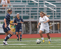 Boston Aztec midfielder Riley Houle (22) brings the ball forward.  In a Women's Premier Soccer League (WPSL) match, Boston Aztec (white) defeated Seacoast United Phantoms (blue), 3-0, at North Reading High School Stadium on Arthur J. Kenney Athletic Field on on June 25, 2013.