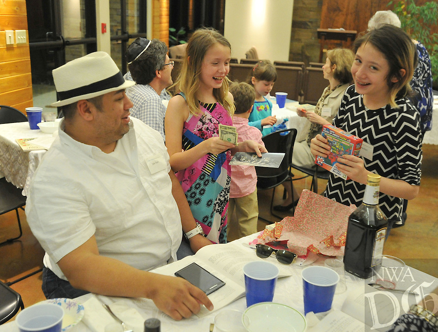 NWA Democrat-Gazette/MICHAEL WOODS &bull; @NWAMICHAELW<br /> Thalia Hart (center) and her sister Lena Hart, open their prizes with their father Jake Hart after the search for the afikomen Saturday, April 23, 2016 during the Passover Seder in Fayetteville.  A traditional activity during the Seder is for adults to hide the afikomen, a ceremonial broken half of matzah, for the children to find at the end of the Seder service.  The child that finds the afikomen gets a special prize while the rest of the participants receive a small gift.
