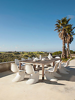 An al fresco dining area on the terrace with a large wooden dining table and white Verner Panton chairs and panoramic views over the rolling hillsides