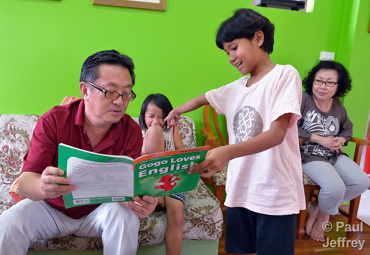 Gary Moon, a United Methodist missionary in Thailand, helps girls with their homework in an orphanage he founded with his wife Cindy (right) in Chiang Mai. The girls are orphans, and are all HIV positive.