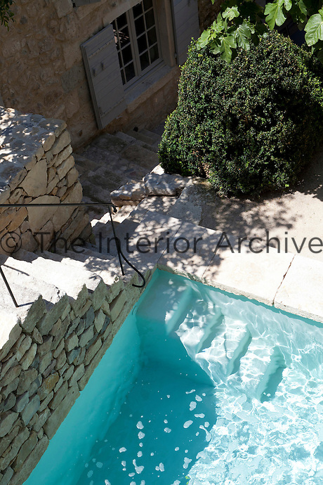 The clear waters of the outdoor swimming pool are enclosed by a textured stone wall