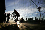 Pedestrains and cyclists make their way across the Brooklyn Bridge in New York.