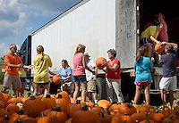 NWA Democrat-Gazette/BEN GOFF @NWABENGOFF<br /> Members of the First United Methodist Church Downtown Bentonville youth group, Kryptonite youth softball team and Downtown Kids unload a truckload of pumpkins on Sunday Sept. 27, 2015 at the church. The volunteers were setting up the church's annual pumpkin patch, which will be open each day of the week from 2-6:00p.m. starting Monday. Proceeds from pumpkin sales will help support a youth mission trip to Haiti in March.