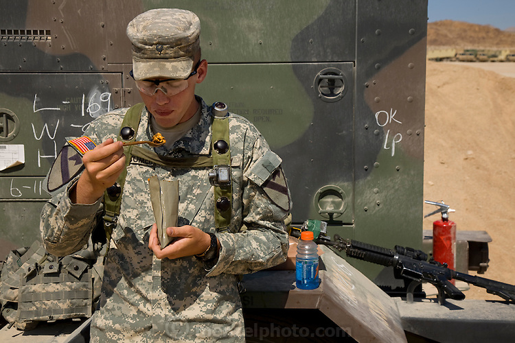 """U.S. Army officer Curtis Newcomer eats chili mac, his favorite MRE, at lunch time at the National Training Center at Fort Irwin in California's Mojave Desert. (From the book What I Eat: Around the World in 80 Diets.) The caloric value of his day's worth of food in the month of September was 4,000 kcals. He is 20; 6'5"""" and 195 pounds. His weapon is fitted with a laser that interacts with receivers worn by all of the soldiers and actors in the training exercise, regardless of duty, rank, or location in the training theater. At left: After the second of three mock battles of the day, Iraqis and Americans playing soldiers, victims, and insurgents relax together in the shade until the next 20 minutes of choreographed crisis. MODEL RELEASED."""