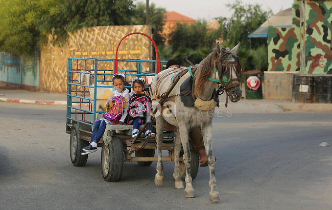 Palestinian schoolchildren ride a horse-drawn cart as they make their way to school on the first day of a new school year, at a United Nations-run school in Deir al-Balah refugee camp in the central Gaza Strip August 23, 2017. Photo by Ashraf Amra