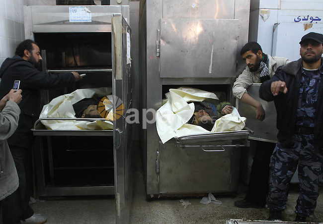 Palestinian relatives look at the bodies of Jihad Al-Hour, 20 and Osama Al-Nabahen, 21, killed by Israeli troops near the Israeli fence on the outskirts of El Bureij refugee camp in the central of Gaza Strip, in the morgue of Al-Aqsa hospital in Deir Al Balah, central Gaza Strip, Monday, Dec. 13, 2010. The Israeli military said troops killed two unarmed Palestinians trying to cross into Israel from Gaza on Saturday.. Photo by Ashraf Amra