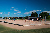 Co-eds athletes play volleyball on a beautiful sunny summer day at the sand volleyball courts in Zilker Park, Austin, Texas.