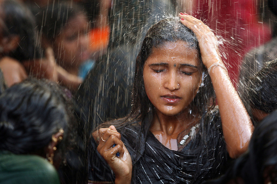 """A young woman bathes in a communal bathing area before worshipping at the Yellamma temple during the Yellamma Jatre (fesival) in Saundatti, India. As part of Yellamma custom, all worshippers must wash before worshipping and during the full moon festical, young girls from impoverished lower caste families are """"married"""" to the goddess Yellamma to appease her.  Once they are married to Yellamma, they are regarded as servants to the goddess and must perform temple duties as well as satisfy the sexual needs of the priests and other men.  They may no longer marry a mortal and often end up being sold by unscrupulous priests to pimps who take them to work in the red-light districts of India's urban areas."""