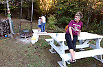 Mrs. Lewis sits on a picnic table at her home as her husband shows their son how to shoot a compound bow on Friday, Oct. 11, 2013. <br /> <br /> Photo by Coty Giannelli