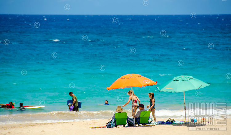 Family with beach umbrella's and two young girls at Hapuna Beach, along the Big island of Hawaii's Kohala coast. This white sand beach has been rated one of the best beaches in the world time and time again