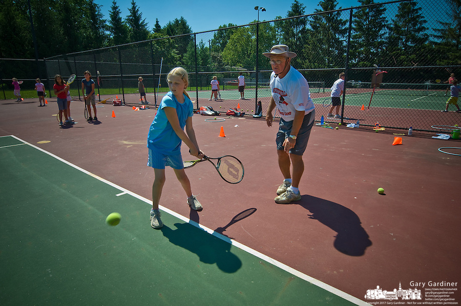 Children receive instructions from their coach at a tennis day camp.