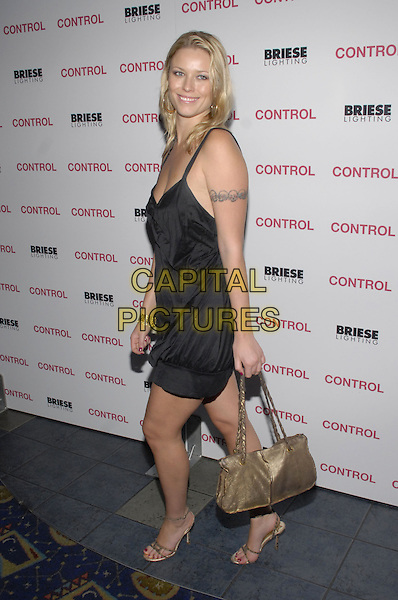 "KIERA CHAPLIN.New York premiere of The Weinstein Company's ""Control"" held at Chelsea West Cinema, New York City, New York, USA..September 25th, 2007.full length black dress gold shoes bag purse bracelet tattoo.CAP/ADM/BL.©Bill Lyons/AdMedia/Capital Pictures. *** Local Caption ***"