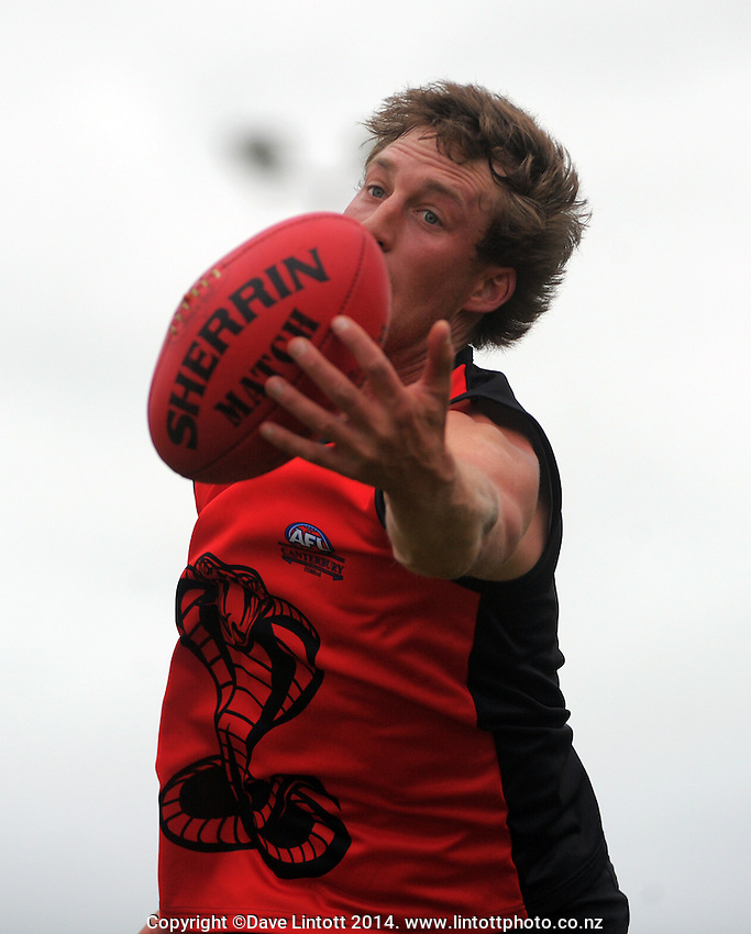 Richie Heazlewood in action during the Wellington Australian Rules Football National Provincial Championship match between the Canterbury Cobras (black and red) and Otago Riot (blue and gold) at Hutt Park, Wellington, New Zealand on Saturday, 6 December 2014. Photo: Dave Lintott / lintottphoto.co.nz