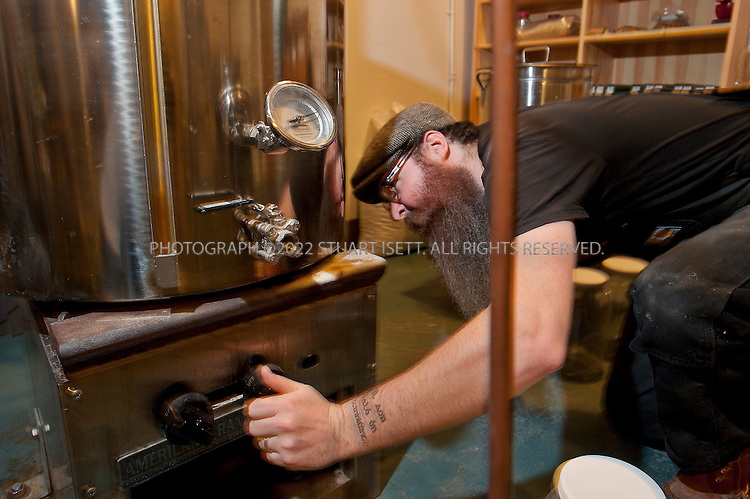 10/13/2011--Seattle, WA, USA..Sound Spirits distiller Kevin Barrans, 32, at work adjusts the temperature on a still....The first craft distillery in Seattle since Prohibition, it's fitting that Sound Spirits sits on 15th Avenue W, just a short amble from downtown and from the water that flows in from the Sound. The company's stylized design sense marries fashionable bottle shapes and a Puget Sound octopus logo and mascot, but what really sets this distillery apart is its flavor profile and the use of Washington malted barley, a grain that comes from the fields of the Palouse, far from Seattle in the state's southeastern corner.. .Opened in September 2010, Sound Spirits is the brain child of distiller (and Boeing engineer) Steven Stone, who continually experimented, tested, researched and tasted a variety of grains before making what could be seen as a curious choice: going with malted barley as a base. There are currently few vodkas and fewer gins that use malted barley as their base grain; for one thing, it's more expensive than other grains. It also adds a large dollop of flavor from the first drop off the still, and many modern vodkas shy away from personality in their taste profiles, going instead for a product that tends to be boringly neutral. But a signature personality and taste is exactly what Stone wanted. And so its Ebb+Flow Vodka ($32) uses 100 percent malted barley, its Ebb+Flow Gin ($33) uses 50 percent, and its newest product (release date wasn't firm at press time), Sound Spirits Aquavit, a Danish-style aquavit, is also based on malted barley. ..Sound Spirits' devotion to malted barley is only matched by its focus on sustainability, with the spent grain going to feed a local farmer's cow and a continuous loop used to save water during the distilling process. While its signature spirits may be named after a mixture of the tides and the Northwest's laid-back nature, Sound Spirits is anything but laid back when it comes to the hunt to de