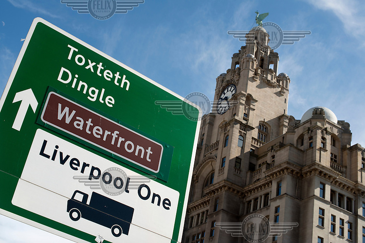 A sign indicates the way to the districts of Toxteth and Dingle on Pier Head a road that passes by the Royal Liver Building in Liverpool.