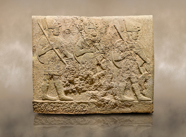 Photo of Hittite sculpted orthostats of Long Wall Limestone, Karkamıs, (Kargamıs), Carchemish (Karkemish), 900-700 BC. Anatolian Civilisations Museum, Ankara, Turkey<br /> <br /> Soldiers. Figure of three helmeted warriors. They have their shield in their back and their spear in their hand. The prisoners in their front are depicted as small. The lower part of the orthostat is decorated with wring / braiding motifs.<br /> <br /> On a brown art background.