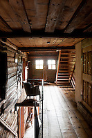 A rustic open staircase leads from the landing up to the bedroom floor
