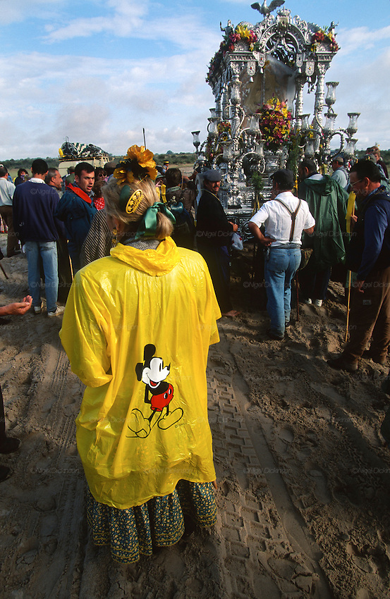 "A pilgrim with a Mickey Mouse poncho walks in the rain. The pilgrim route of the Hermandade de Sanlucar de Barrameda from Sanlucar across the Parque Donana to El Rocio, Huelva Province, Andalusia, Spain...El Rocio follows on from Semana Santa - Easter week and the various spring ferias, of which Seville's Feria de Abril (April) is the biggest. The processions to the (Hermitage) Hermita de El Rocío, at Pentecost, is the most famous (Romeria) pilgrimage in the Andalusian region, attracting nearly a million people from across Andalusia, Spain and the world. The cult started off in the 13th century when a statue of the virgin Mary was apparently found in a tree trunk in the Donana Park. What was first a local devotion at Pentecost by local pilgrim brotherhoods ""hermandades"" became by the 19th century into dozens of fraternities developed from such as Cadiz, Selville and Huelva. Some walk for several days, others travel with oxen drawn wagons or on horseback, with traction engines and all terrain vehicles, camping along the trail they take. They wear Andalusian costumes, tight breeches, boots, short jackets and frilly flamenco skirts. Many festivities, flamenco dance, laments, songs and music are combined with religious prayers. Devout pilgrims walk as a penance, keeping vows of silence. An emblem of the immaculate conception (sin peche) is carried. On the Pentecost after the stroke of midnight on the whit Sunday the virgin Mary is carried from the church through the streets of El Rocio by each hermandade to visit each brotherhood's shrine."