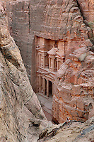 Treasury of the Pharaohs or Khazneh Firaoun, 100 BC - 200 AD, seen through gaps in the rock, Petra, Ma'an, Jordan. Originally built as a royal tomb, the treasury is so called after a belief that pirates hid their treasure in an urn held here. Carved into the rock face opposite the end of the Siq, the 40m high treasury has a Hellenistic facade with three bare inner rooms. Petra was the capital and royal city of the Nabateans, Arabic desert nomads. Picture by Manuel Cohen