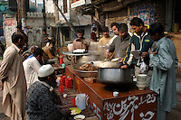 A crowd enjoys breakfast at one of many busy outside restaurants in the Old City of Lahore.