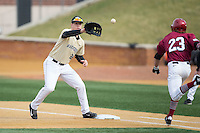 Gavin Sheets (24) of the Wake Forest Demon Deacons waist for a throw as Trent Bryan (23) of the Harvard Crimson hustles down the first base line at David F. Couch Ballpark on March 5, 2016 in Winston-Salem, North Carolina.  The Crimson defeated the Demon Deacons 6-3.  (Brian Westerholt/Four Seam Images)