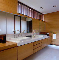 The master bathroom has a pair of wash basins and bespoke oak cabinetry