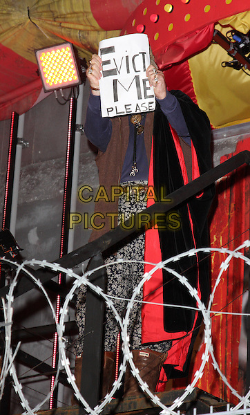 JOHN McCRIRICK .Big Brother 11 Final and Launch night of 'Ultimate Big Brother' at Elstree Studios, Borehamwood, Herts, England, UK, .24th August 2010.full 3/4 length sign banner 'evict me please' fur hat ear flaps deer stalker  cloak brown blue velvet  BB11 BB.CAP/ROS.©Steve Ross/Capital Pictures