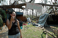 """Pamela DeBaun smokes  acigarette under her for sale sign at her home in Bay St. Louis after Hurricane Katrina severely damaged and flooded her home. The sign reads""""cut little fixer upper-handymans special-call 1-800-CALLFEMA"""" Sept. 16,2005.Photo ©Suzi Altman"""
