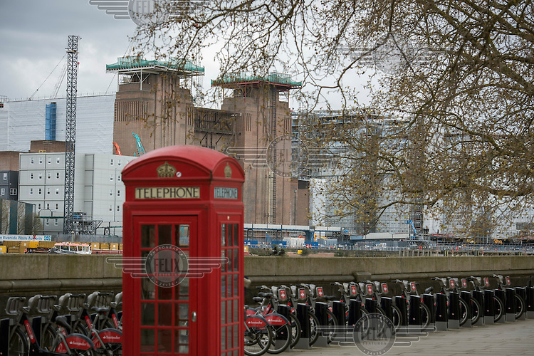A red telephone box in the Nine Elms development site and Battersea Power Station.