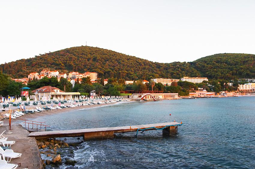Empty Beach, jetty and hotels in evening sunlight sunset. Uvala Sumartin bay between Babin Kuk and Lapad peninsulas. Dubrovnik, new city. Dalmatian Coast, Croatia, Europe.
