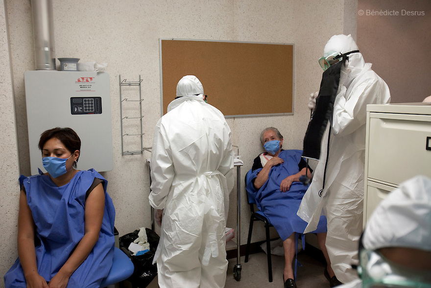 30 april  2009 - Mexico City, Mexico - Doctors wearing full body protective gear examines patients inside the emergency area set up to treat people with flu-like symptoms at the Naval hospital in Mexico City..Mexico opened up its newly built national naval hospital to civilians to deal with the overwhelming number of suspected swine flu cases. Staffers wore goggles, masks and booties to protect themselves while treating patients. The high quality of care stands in stark contrast to most neighborhood hospitals in Mexico City which don't have the staff or resources to deal with the influx of new Flu cases. World health officials raised a global alert to an unprecedented level as the swine flu was blamed for more deaths in Mexico and the epidemic crossed new borders, with the first cases confirmed Tuesday in the Middle East and the Asia-Pacific regionPhoto credit: Benedicte Desrus / Sipa Press