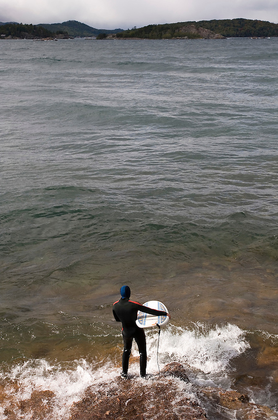 A surfer waits for waves on Lake Superior at Presque Isle Park in Marquette Michigan.