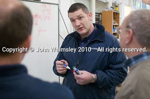 Plumbing students listen to an instructor, Able Skills, Dartford, Kent.