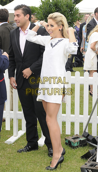 """James """"Arg"""" Argent  & Lydia Bright .The Duke of Essex Polo Trophy at Gaynes Park, Epping, England, UK,.July 9th 2011..full length black suit pink shirt towie white dress one sleeve shoes  side hands funny gesture .CAP/CAN.©Can Nguyen/Capital Pictures."""