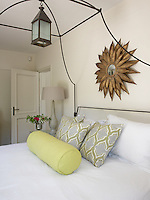 A cool colour scheme of cream and white is brought to life by touches of yellow and two cushions covered in a patterned fabric