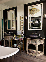 In the master bathroom, demilune tables are fitted with Kohler sinks and Lefroy Brooks fixtures, the sconces are by Porta Romana, and the walls are painted in Farrow & Ball's Mahogany