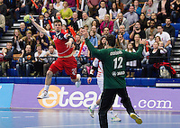 08 JAN 2012 - LONDON, GBR - Great Britain left wing John Pearce (#27, in red) leaps to shoot past Austrian goalkeeper Nikola Marinovic (#12, in green and black) during the men's 2013 World Handball Championships qualification match at the National Sports Centre in Crystal Palace, Great Britain (PHOTO (C) 2012 NIGEL FARROW)