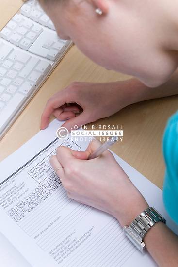 Teenaged girl on work experience placement from school filling out her school assessment book,