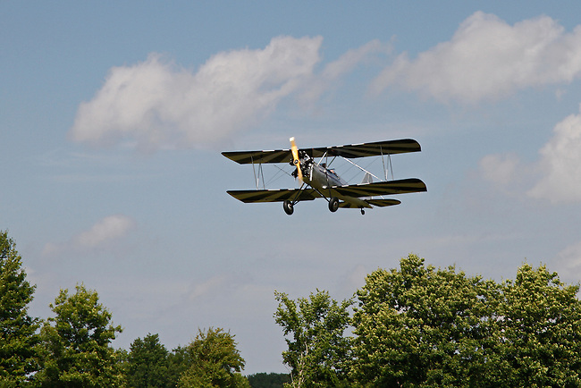 A silver-bodied, Meyers OTW (out-to-win) bi-plane with black and white striped wings climbs over the tree tops into a cloud-filled, blue sky at the 2010 Wings 'n' Wheels Showcase.