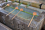 Kyoto City, Japan<br /> Yasaka Shrine, (Shinto) Gion district, bamboo ladles resting on hishaku (rack) over a chuzua (ritual washing  water trough)