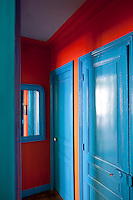 The doors, skirting boards and mirror frame have all been painted bright blue which contrasts fabulously with the bright red walls