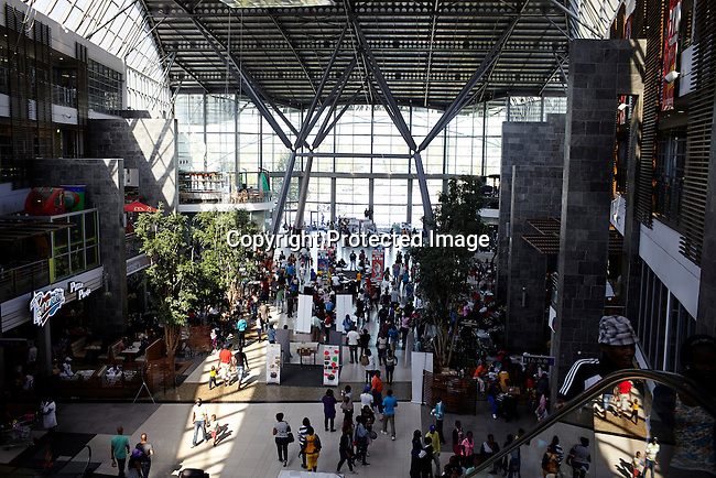 SOWETO, SOUTH AFRICA MAY 1: Shoppers inside a mall on May 1, 2013 at Maponya shopping Mall, Soweto, South Africa.  Maponya is one of several new shopping malls in the township. Soweto today is a mix of old housing and newly constructed townhouses. The population in Soweto is estimated to be around one million people. A new hungry black middle-class is growing steadily. Many residents work in Johannesburg but the last years many shopping malls have been built, and people are starting to spend their money in Soweto. (Photo by: Per-Anders Pettersson)