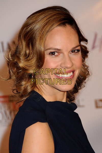 HILARY SWANK .Attending the Hollywood Reporter's 18th Annual Women In Entertainment Breakfast held at the Beverly Hills Hotel, Beverly Hills, California, USA, .4th December 2009..portrait headshot smiling earrings gold dangly wav hair navy blue .CAP/ADM/BP.©Byron Purvis/Admedia/Capital Pictures