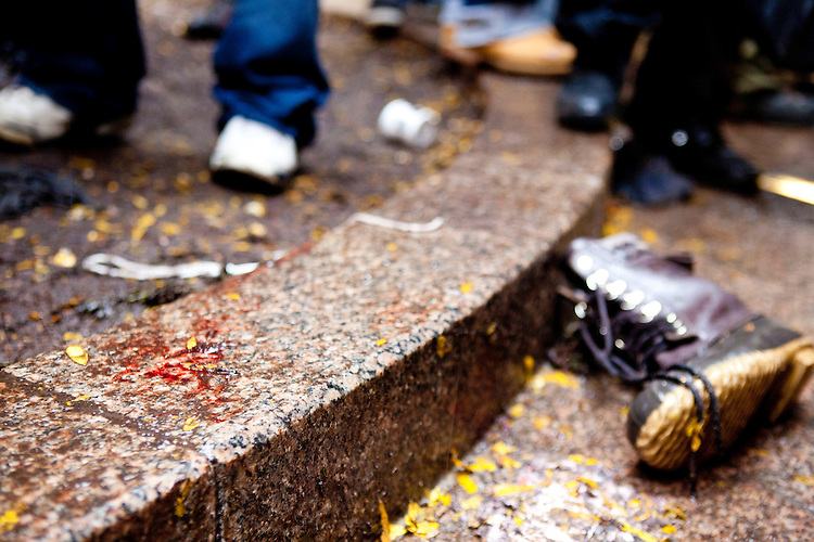 """After a slight altercation with a protester the NYPD responds with a heavy hand in Zuccotti Park on November 17, 2011 in New York City.  After subduing the perpetrator, who wound up bleeding profusely from his head (his blood and boot shown here), the police were jeered by hundreds of protesters with the chant, """"Get out of our park!"""""""