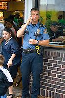 Policeman checking in with his cell phone in front of fast food restaurant. Cinco de Mayo Fiesta St Paul Minnesota USA