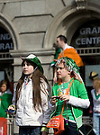 Two young girls watching the Dublin St. Patrick's Day Parade, on O'Connell Street.