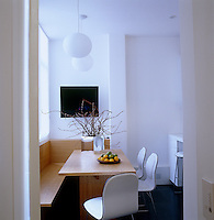 The breakfast area in the kitchen has a custom-built wooden bench and table lit by pendant lights