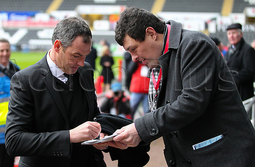 February 12th 2017, Liberty Stadium, Swansea, Wales; Premier league football, Swansea versus Leicester City; Swansea City's Manager Paul Clement signs a programme for a fan before the match